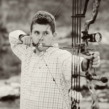 A young man shooting a bow and arrow.
