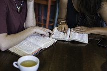 women reading Bibles around a table at a Bible study