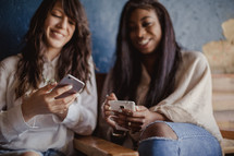 young women checking cellphones and texting