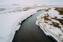 snow along the edge of a stream