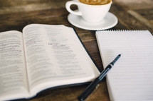 cappuccino and an open Bible and notepad and pen