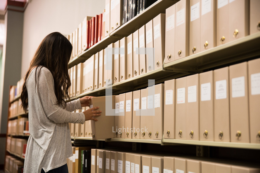 woman looking for periodicals in a library