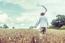 a man with a Scythe blade walking in a wheat field