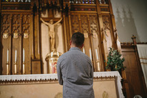Young man praying in front of tabernacle in Catholic church