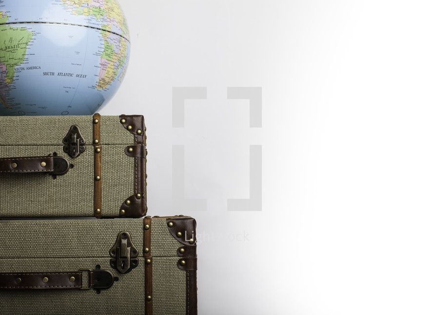 a globe on stacked suitcases