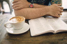 cappuccino and a man reading a Bible in a coffee shop