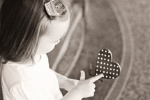 a girl child holding a heart