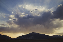 Sun rays breaking through the clouds over a snow capped mountain