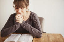 woman with her hands folded in prayer over a Bible