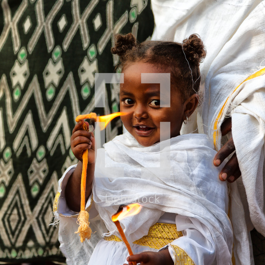 little girl holding flames at a celebration in Ethiopia
