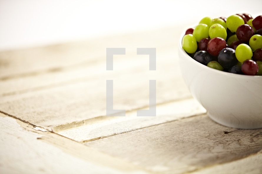 A bowl of grapes sit on a wooden table.