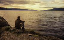 a man sitting on a rocky shore praying