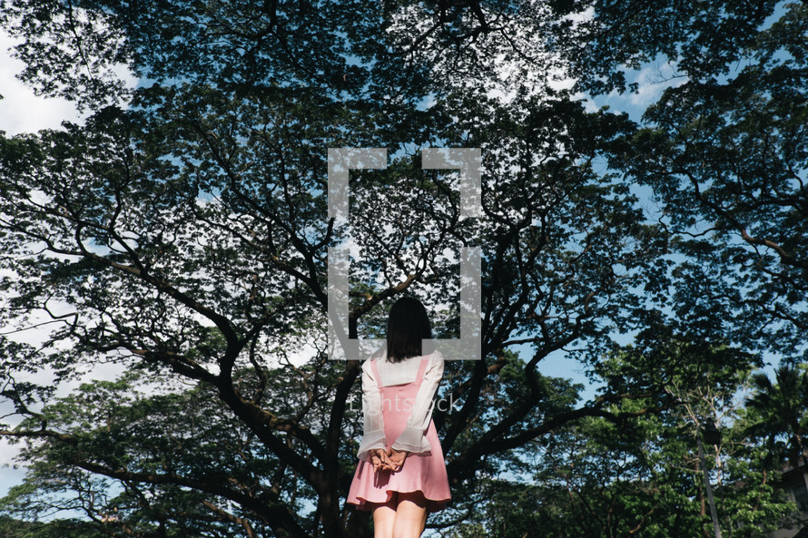 a girl standing in front of spring trees
