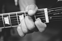 Man's hand holding neck of guitar.