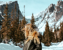 woman standing in a valley near snow covered mountains