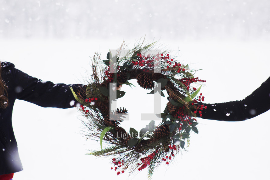 women holding a Christmas wreath