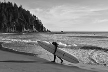 a man carrying a surfboard on a beach