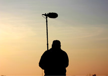 Silhouette of a production assistant holding sound equipment.