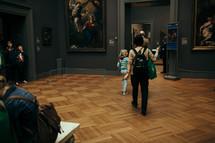 people walking through an art museum
