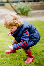 Child finding Easter eggs in the grass.