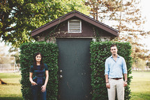 a man and a woman standing apart in front of a shed