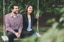 a happy couple sitting on a swing