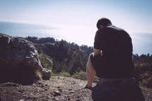 Contemplating man sitting on a rock in the mountains.