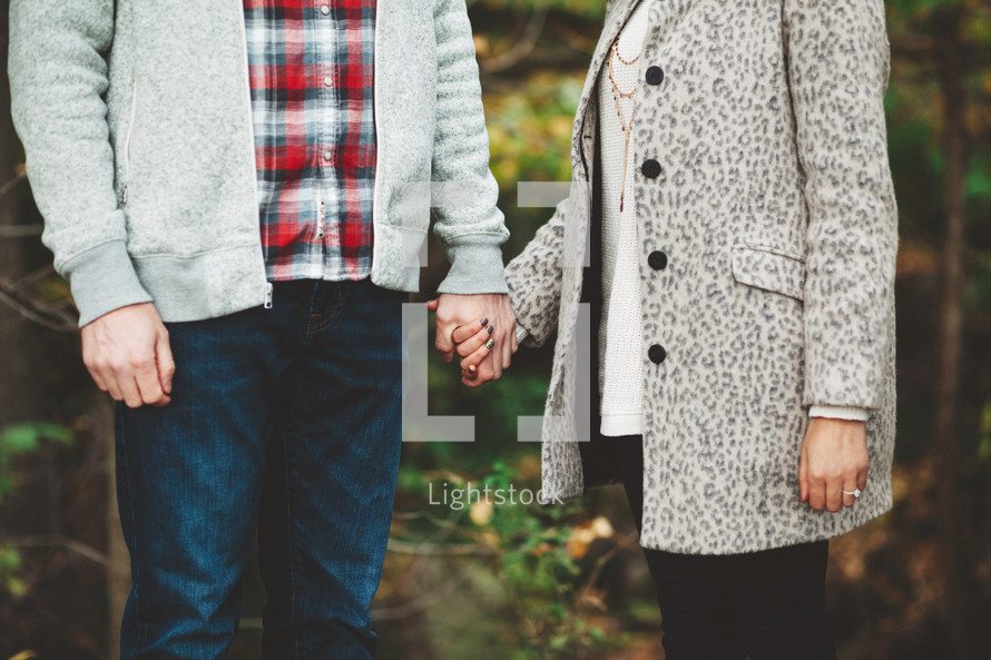 a couple in sweaters holding hands