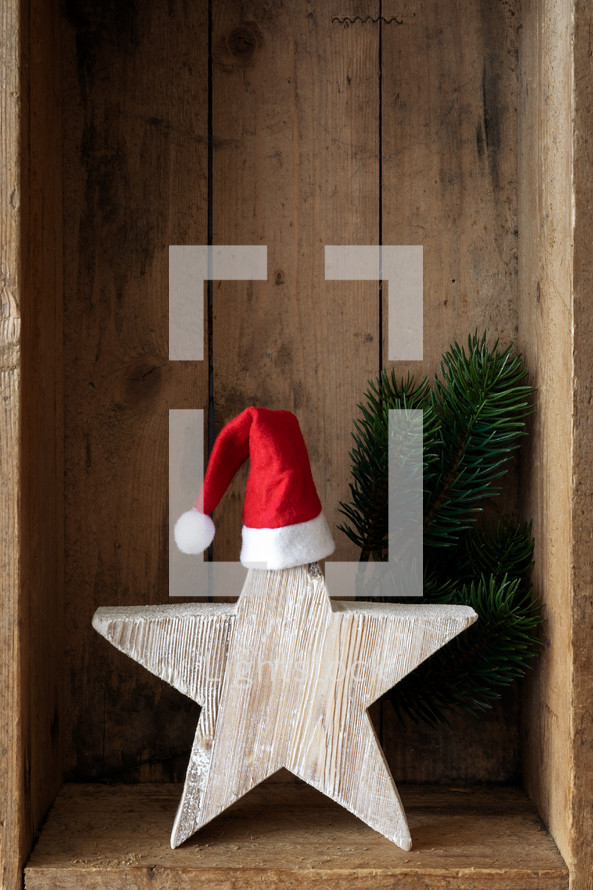 Christmas star with a santa hat in a wooden crate