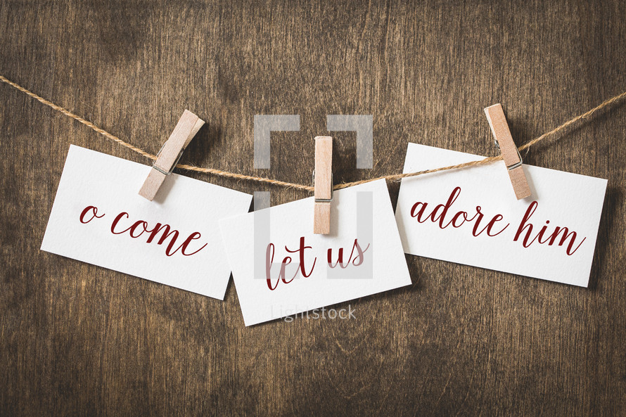 words o come let us adore him on card stock hanging on twine by a clothespin
