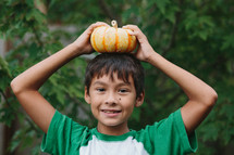 boy with a pumpkin on his head