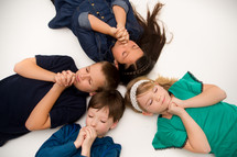 Children praying with their eyes closed while laying on the ground.