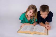 Siblings reading the Bible together on the floor.