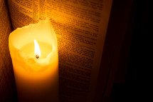 Burning candle next to a Bible open to Hebrews 12.