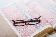 Glasses on the pages of a Bible open to the Book of John.