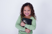 Smiling girl holding a closed Bible.