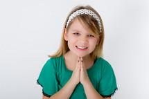 Smiling girl praying.