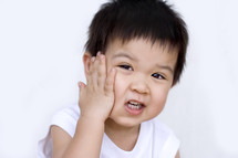 a toddler boy with his hand on his face