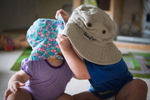 A small boy and girl wearing big hats.