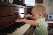infant playing a piano