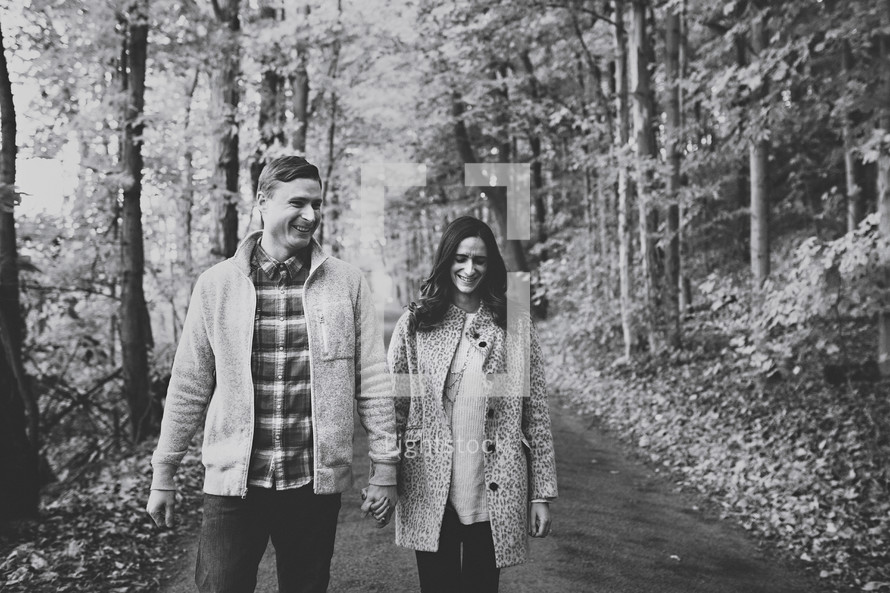 a couple walking holding hands on a paved path