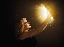woman holding up a glowing Bible