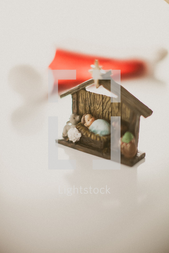 The Manger scene in front of a red Santa hat