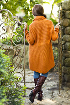 A young woman in a sweater standing between gates orange