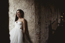 Bride smiling, leaning against a stone wall