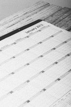 Day planner open to January 2013 on wooden table.