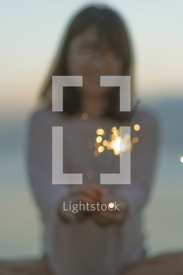 a young woman holding a sparkler on a beach
