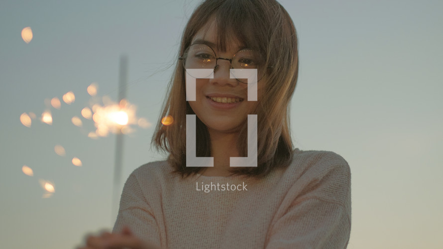 a young woman holding a sparkler