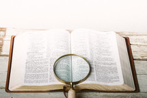 Magnifying glass laying on top of pages of Bible open to Isaiah 12-13 laying on wooden table.
