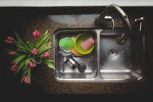 dirty dishes in a sink and flowers